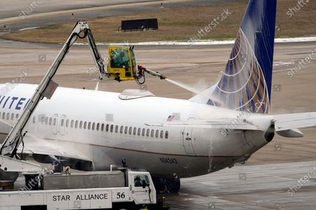 Stock Picture of United Airlines jet is deiced at George Bush Intercontinental Airport, in Houston. Airport officials said crews are still working to clear thick patches of ice off of the airfield. They expect the airfield to open later this evening after being closed for days due to the severe cold weather which blanketed the area with snow and ice