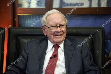 """In this May 7, 2018, photo, Berkshire Hathaway Chairman and CEO Warren Buffett smiles during an interview in Omaha, Neb., with Liz Claman on Fox Business Network's """"Countdown to the Closing Bell."""" Buffett's company made major new investments in Verizon and Chevron and again trimmed its huge stake in Apple while making several other adjustments to its stock portfolio in 2020. Berkshire Hathaway said in a regulatory filing, that it bought $8.6 billion worth of Verizon stock and picked up $4 billion worth of Chevron shares over the last six months of 2020"""