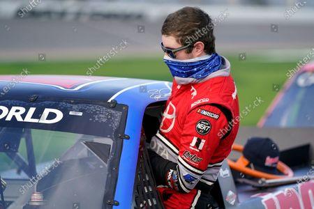 Spencer Davis climbs in his car during NASCAR truck qualifying at Daytona International Speedway, in Daytona Beach, Fla
