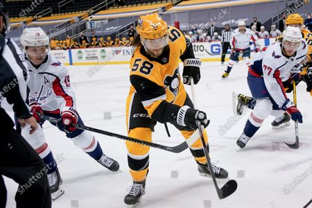 Pittsburgh Penguins' Kris Letang (58) gets between Washington Capitals' Nicklas Backstrom (19) and T.J. Oshie (77) as he pursues the puck during the second period of an NHL hockey game, in Pittsburgh