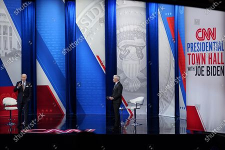 President Joe Biden speaks during a televised town hall event at Pabst Theater, in Milwaukee, as moderator Anderson Cooper listens at right
