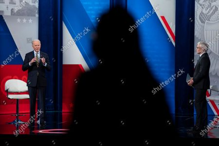 Anderson Cooper listens as President Joe Biden speaks during a televised town hall event at Pabst Theater, in Milwaukee