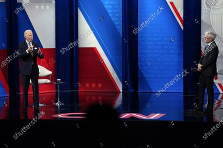 President Joe Biden talks as Anderson Cooper listens during a televised town hall event at Pabst Theater, in Milwaukee