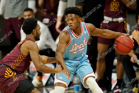 Stock Image of Drake guard Joseph Yesufu drives around Loyola of Chicago guard Keith Clemons, left, during the first half of an NCAA college basketball game, in Des Moines, Iowa