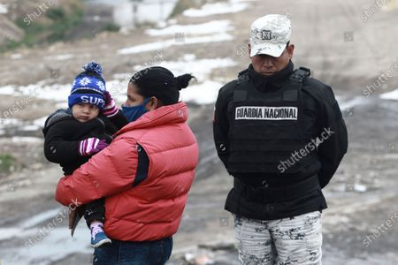 Cuban migrant family is apprehended by the National Guard before crossing the Rio Bravo on the border with the U.S. in Ciudad Juarez, Chihuahua state, Mexico, . The number of people apprehended at the U.S.-Mexico border has increased since Jan. with migrant families crossing from Ciudad Juarez and turning themselves over to Border Patrol