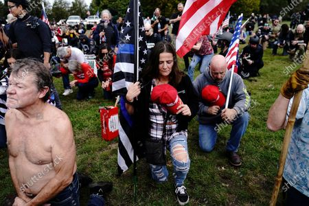 Members of the Proud Boys and other right-wing demonstrators kneel in prayer at a rally, in Portland, Ore. Alex DiBranco, executive director of the Institute for Research on Male Supremacism, said there are differences among Proud Boys chapters over whether to embrace women as Proud Girls or not, even as the group as a whole has become more hostile to women's auxiliaries over the past couple of years
