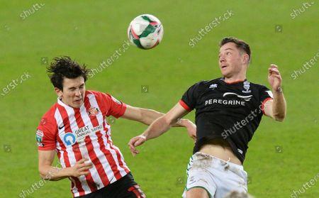 Luke O'Nien of Sunderland vies for the ball with Tom Hopper of Lincoln City
