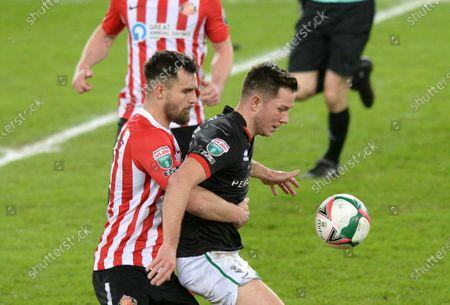 Tom Hopper of Lincoln City fends off Bailey Wright of Sunderland