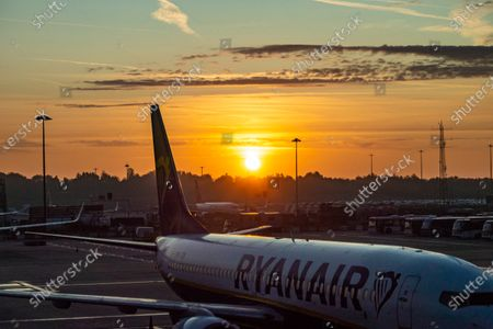 Early morning magic hour sunrise scenery in London Stansted STN EGSS airport, with aircraft of Ryanair FR RYR  Irish low-cost carrier, Boeing 737-800 airplane parked at the tarmac of the apron in front of the gates of the airport terminal. The world passenger traffic declined during the Covid-19 Coronavirus pandemic due to the lockdown and travel restriction with the aviation industry struggling to survive needing government financial aid, having the fleet grounded while asking travelers to wear facemask, have negative tests or stay isolated in quarantine.
