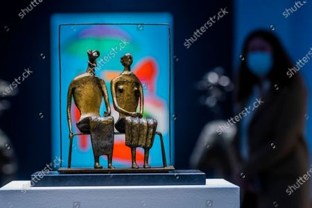 Stock Image of Henry Moore, Maquette for King and Queen, conceived and cast in 1952, estimate: £750,000-1,000,000 with Sir Michael Craig-Martin, With Red Shoes, Painted in 2000, Estimate: £60,000-80,000 - Behind Closed Doors: Preparations Take Place at Christie's for the livestreamed Modern British Art Auction on 1 March 2021.