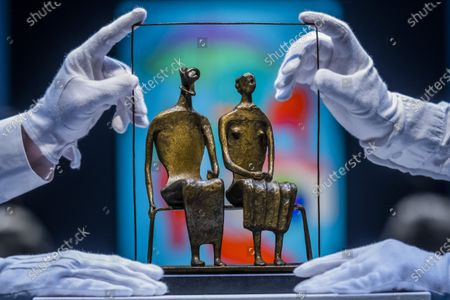 Stock Photo of Henry Moore, Maquette for King and Queen, conceived and cast in 1952, estimate: £750,000-1,000,000 with Sir Michael Craig-Martin, With Red Shoes, Painted in 2000, Estimate: £60,000-80,000 - Behind Closed Doors: Preparations Take Place at Christie's for the livestreamed Modern British Art Auction on 1 March 2021.