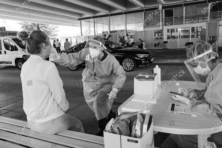 Black and White B/W photo of a female healthcare worker collects from a female passenger sample for covid testing. Travelers in cars and buses from all over Europe but mostly from Bulgaria, Romania, Czech Republic and Poland arrive at the Greek Bulgarian borders of Promahonas - Kulata, entering point in Greece for holidays and they are checked for Coronavirus. Greece lifted the travel ban since July 1 and relaunched the tourism season. Arriving tourists should carry the special Passenger Locator Form for each individual, a new required document to enter Greece for all the arriving people and the increased Covid-19 Coronavirus tests that are applied to most of the arriving cars, based on a special algorithm. Greece increased the testing capacity with the health crew of the National Public Health Organization EODY at the land borders. Greece will allow the entrance only to passengers with up to 72 hours prior to the arrival Covid-19 test with negative results in English from a certified laboratory. In August 2020 Greece is starting implementing new protective measures like local lockdown, changing the maximum number of people together and the working hours of restaurants, bars, beach bar etc against the spread of the pandemic outbreak, as people relax and avoid the guidelines. Until now Greece is counting 263 fatalities from the virus.