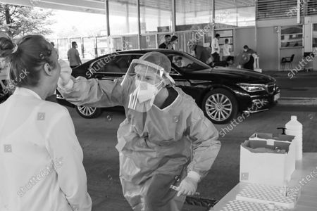 Stock Photo of Black and White B/W photo of a female healthcare worker collects from a female passenger sample for covid testing. Travelers in cars and buses from all over Europe but mostly from Bulgaria, Romania, Czech Republic and Poland arrive at the Greek Bulgarian borders of Promahonas - Kulata, entering point in Greece for holidays and they are checked for Coronavirus. Greece lifted the travel ban since July 1 and relaunched the tourism season. Arriving tourists should carry the special Passenger Locator Form for each individual, a new required document to enter Greece for all the arriving people and the increased Covid-19 Coronavirus tests that are applied to most of the arriving cars, based on a special algorithm. Greece increased the testing capacity with the health crew of the National Public Health Organization EODY at the land borders. Greece will allow the entrance only to passengers with up to 72 hours prior to the arrival Covid-19 test with negative results in English from a certified laboratory. In August 2020 Greece is starting implementing new protective measures like local lockdown, changing the maximum number of people together and the working hours of restaurants, bars, beach bar etc against the spread of the pandemic outbreak, as people relax and avoid the guidelines. Until now Greece is counting 263 fatalities from the virus.