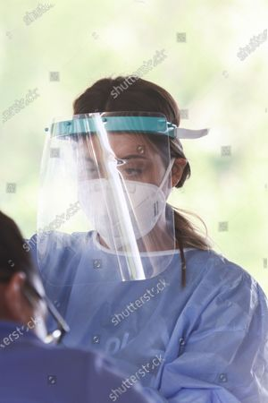 Closeup portrait of a female healthcare worker holding a covid test sample. Travelers in cars and buses from all over Europe but mostly from Bulgaria, Romania, Czech Republic and Poland arrive at the Greek Bulgarian borders of Promahonas - Kulata, entering point in Greece for holidays and they are checked for Coronavirus. Greece lifted the travel ban since July 1 and relaunched the tourism season. Arriving tourists should carry the special Passenger Locator Form for each individual, a new required document to enter Greece for all the arriving people and the increased Covid-19 Coronavirus tests that are applied to most of the arriving cars, based on a special algorithm. Greece increased the testing capacity with the health crew of the National Public Health Organization EODY at the land borders. Greece will allow the entrance only to passengers with up to 72 hours prior to the arrival Covid-19 test with negative results in English from a certified laboratory. In August 2020 Greece is starting implementing new protective measures like local lockdown, changing the maximum number of people together and the working hours of restaurants, bars, beach bar etc against the spread of the pandemic outbreak, as people relax and avoid the guidelines. Until now Greece is counting 263 fatalities from the virus.