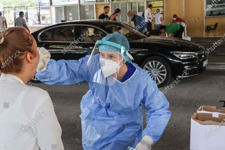 A female healthcare worker collects from a female passenger sample for covid testing. Travelers in cars and buses from all over Europe but mostly from Bulgaria, Romania, Czech Republic and Poland arrive at the Greek Bulgarian borders of Promahonas - Kulata, entering point in Greece for holidays and they are checked for Coronavirus. Greece lifted the travel ban since July 1 and relaunched the tourism season. Arriving tourists should carry the special Passenger Locator Form for each individual, a new required document to enter Greece for all the arriving people and the increased Covid-19 Coronavirus tests that are applied to most of the arriving cars, based on a special algorithm. Greece increased the testing capacity with the health crew of the National Public Health Organization EODY at the land borders. Greece will allow the entrance only to passengers with up to 72 hours prior to the arrival Covid-19 test with negative results in English from a certified laboratory. In August 2020 Greece is starting implementing new protective measures like local lockdown, changing the maximum number of people together and the working hours of restaurants, bars, beach bar etc against the spread of the pandemic outbreak, as people relax and avoid the guidelines. Until now Greece is counting 263 fatalities from the virus.