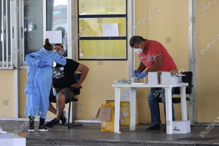 A female healthcare worker collects covid-19 sample from a male passenger. Travelers in cars and buses from all over Europe but mostly from Bulgaria, Romania, Czech Republic and Poland arrive at the Greek Bulgarian borders of Promahonas - Kulata, entering point in Greece for holidays and they are checked for Coronavirus. Greece lifted the travel ban since July 1 and relaunched the tourism season. Arriving tourists should carry the special Passenger Locator Form for each individual, a new required document to enter Greece for all the arriving people and the increased Covid-19 Coronavirus tests that are applied to most of the arriving cars, based on a special algorithm. Greece increased the testing capacity with the health crew of the National Public Health Organization EODY at the land borders. Greece will allow the entrance only to passengers with up to 72 hours prior to the arrival Covid-19 test with negative results in English from a certified laboratory. In August 2020 Greece is starting implementing new protective measures like local lockdown, changing the maximum number of people together and the working hours of restaurants, bars, beach bar etc against the spread of the pandemic outbreak, as people relax and avoid the guidelines. Until now Greece is counting 263 fatalities from the virus.