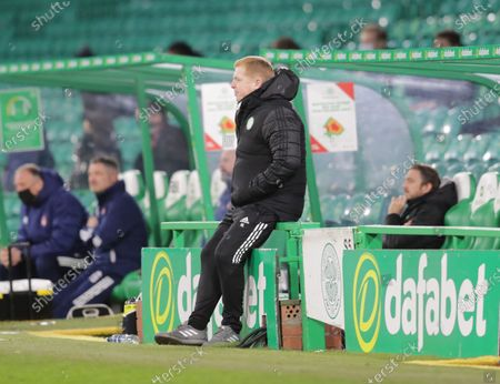 Celtic Manager Neil Lennon sits on an advertising board next to the dugout