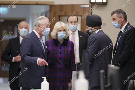 Britain's Prince Charles and Camilla, Duchess of Cornwall talk with Chief Pharmacist Inderjit Singh, second right, during a visit to the Queen Elizabeth Hospital in Birmingham, England, to thank volunteers undertaking clinical trials for the COVID-19 vaccinations