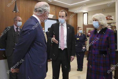 Britain's Prince Charles and Camilla, Duchess of Cornwall talk with Health Secretary Matt Hancock, left, during a visit to the Queen Elizabeth Hospital in Birmingham, England, to thank volunteers undertaking clinical trials for the COVID-19 vaccinations