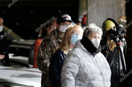 Stock Image of Spectators and photographers gather on the tenth floor of an adjacent parking garage to observe the Trump Plaza Hotel and Casino on the Atlantic City Boardwalk being imploded and brought down with high explosives in Atlantic City, New Jersey, USA, 17 February 2021. The Trump Plaza Hotel and Casino operated from 1984 to 2014 along the Atlantic City Boardwalk. In the 1990's Former US President Donald J. Trump owned and operated four casino's in Atlantic City, since then Trump Entertainment Resorts and its predecessors have filed for Chapter 11 bankruptcy protection four times, in 1991, 2004, 2009, and 2014. The demolished property is currently owned by billionaire investor Carl Icahn, a Trump confidante.