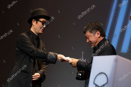 Lily Franky (L) and Japanese director Hirokazu Kore-Eda receives the Donostia Award in recognition of his prestigious film career during the 66th San Sebastian Film Festival, in the northern Spanish Basque city of San Sebastian on September 23, 2018.