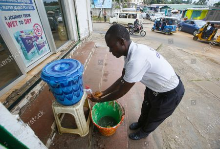 A man washes his hands in chlorinated water as a government measure to prevent the outbreak of Ebola, Monrovia, Liberia 17 February 2021.  According to a statement from the office of Liberian President George Weah on 14 February 2021 the president has placed Liberia's health authorities on an increased alert level following the death of four people from Ebola in neighbouring Guinea marking five years since the last cases were recorded.