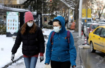 Women wearing masks to help protect against the spread of coronavirus, walk along a busy street, in Ankara, Turkey, . Turkish President Recep Tayyip Erdogan said Wednesday the country will as of March begin to ease restrictions aimed at slowing the spread of coronavirus in provinces where infection rates are low