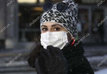 Turkish teacher Aysegul Cepoglu wearing a mask to help protect against the spread of coronavirus, walks along a busy street, in Ankara, Turkey, . Turkish President Recep Tayyip Erdogan said Wednesday the country will as of March begin to ease restrictions aimed at slowing the spread of coronavirus in provinces where infection rates are low