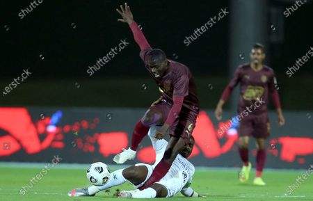 Stock Photo of Al-Ahli's player Motaz Hawsawi (down) in action against Al-Ain's Badou Ndiaye (up) during the Saudi Professional League soccer match between Al-Ahli and Al-Ain at King Abdullah Sport City Stadium, 30 kilometers north of Jeddah, Saudi Arabia, 17 February 2021.