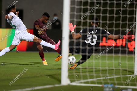 Al-Ahli's player Mohammed Al-Fatil (L) and goalkeeper Mohammed Al-Owais (R) in action against Al-Ain's Amadou Moutari (C) during the Saudi Professional League soccer match between Al-Ahli and Al-Ain at King Abdullah Sport City Stadium, 30 kilometers north of Jeddah, Saudi Arabia, 17 February 2021.