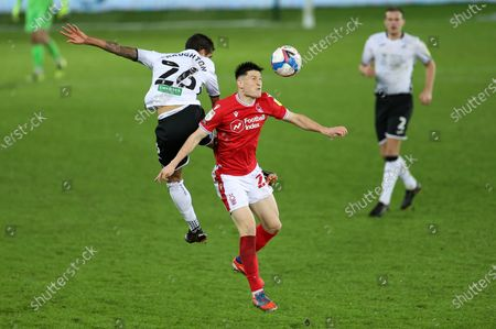 Joe Lolley of Nottingham Forest goes up for the ball with Kyle Naughton of Swansea City.