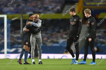 Everton's Fabian Delph, second left, hugs his old teammate Manchester City's Raheem Sterling, watched by John Stones, third left, and Kevin De Bruyne, right, before the English Premier League soccer match between Everton and Manchester City at Goodison Park stadium, in Liverpool, England