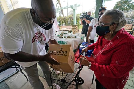 Former Miami Heat basketball player Glen Rice, left, loads a box of food into the cart of Eva Everett, 86, during a food distribution event at the Mildred and Claude Pepper Towers apartments in Miami. The Heat, Ultimate Kronos Group, Feeding South Florida and Pollo Tropical surprised about 200 seniors at two low-income housing locations with boxes of food as part of National Random Acts of Kindness Day