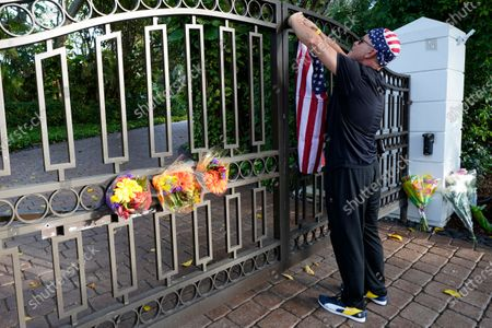 John Hensel attaches an American flag to the gate of the home of his friend and talk radio host Rush Limbaugh, in Palm Beach, Fla. Limbaugh, 70, died this morning of lung cancer