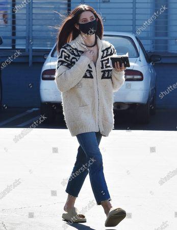Ashley Greene wears her mask as she picks up sushi