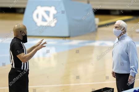 North Carolina head coach Roy Williams speaks with an official during the first half of an NCAA college basketball game against Northeastern in Chapel Hill, N.C