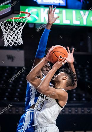 Wake Forest forward Ody Oguama (33) shoots as he is fouled by Duke center Mark Williams duirng an NCAA college basketball game, in Wintson-Salem, N.C