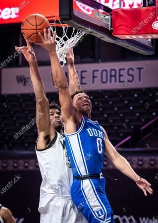 Stock Image of Duke forward Wendell Moore Jr. (0) shoots as Wake Forest center Emmanuel Okpomo (30) defends during an NCAA college basketball game, in Wintson-Salem, N.C