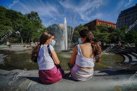 Two women wearing masks enjoys the weather in front of the fountain at Washington Square Park as New York City continues Phase 4 of re-opening following restrictions imposed to slow the spread of coronavirus on August 20, 2020 in New York City. The fourth phase allows outdoor arts and entertainment, sporting events without fans and media production.