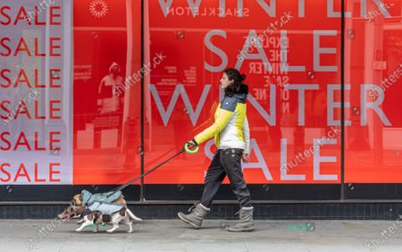 Members of the public walk past Winter Sale signs at the Peter Jones store in Chelsea, South West London as Downing Street mulls over how and when to unlock the country from coronavirus restrictions. Yesterday, Prime Minister Boris Johnson revealed that the relaxation of restrictions would be done in stages and would focus on the data not on dates for the easing of lockdown with pubs and hospitality being the last to reopen.