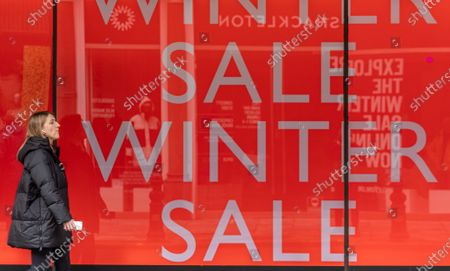Stock Photo of Members of the public walk past Winter Sale signs at the Peter Jones store in Chelsea, South West London as Downing Street mulls over how and when to unlock the country from coronavirus restrictions. Yesterday, Prime Minister Boris Johnson revealed that the relaxation of restrictions would be done in stages and would focus on the data not on dates for the easing of lockdown with pubs and hospitality being the last to reopen.
