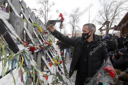 A man lays flowers to the Heavenly Hundred monument during the anniversary. Ukrainians commemorated the 7th anniversary of the eruption of the Euro Maidan revolution, an uprising against the government of the then Ukrainian President Viktor Yanukovych, in which at least 100 protestors died.