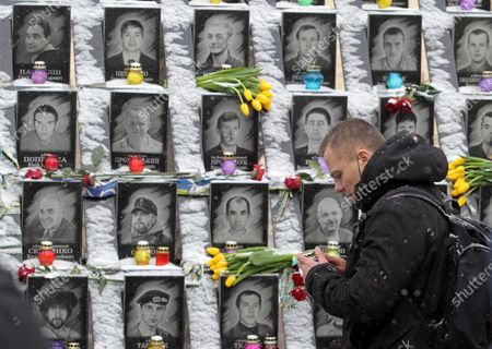 Stock Image of A man holding a candle standing next to portraits of Heavenly Hundred protesters during the anniversary. Ukrainians commemorated the 7th anniversary of the eruption of the Euro Maidan revolution, an uprising against the government of the then Ukrainian President Viktor Yanukovych, in which at least 100 protestors died.