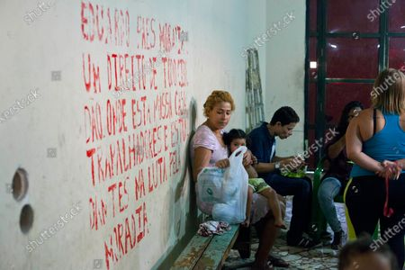 """Stock Photo of The Lobby of the Planatu Hotel. This is were the families spend time with their children and prepare meals. The wall reads """"Eduardo Paes! Housing is a right of all citizens, where are our homes? Workers and students in the fight for housing.""""    These families having been occupying buildings for quite a long time in Rio de Janeiro. Some of them have been moving around for years while others have just now had to hold space to have a shelter for themselves and their children. Due to the rampant gentrification that's been spreading through Rio in the wake of the World Cup and the up coming Olympics many have been shoved to the edge financially and have been forced out through rising rents or being evicted by the Brazilian Military Police. They are occupying these buildings to use them as a bargaining tool with the city government. These buildings are all in desirable areas for development so the families are hoping that they can argue their case for social assistance by holding these spaces. They know the city wants to be able to demolish and sell the land the building are on to developers that are gentrifying Rio de Janeiro. By holding these spaces they effectively holding on to something the city wants and they believe they can use that as a bargaining tool to get more social assistance. Many were promised money when they left the favelas. The vast majority have not received the money or have had the city government try to divide them so that only some will get the money. The families have stuck together and have refused partial payments because they believe that the government will with hold the rest of the payments to the other families. After refusing payments the state and city of Rio de Janeiro has reacted violently and evicted them from various other occupations. Most of the evictions are either dawn or midnight raids with tear gas and rubber bullets being shot at the occupations or those dwelling inside the occupations."""