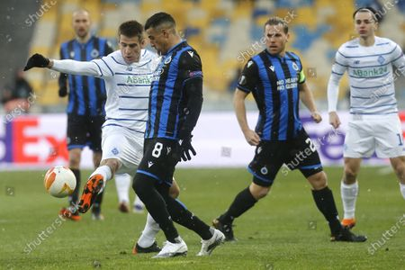 Dynamo Kyiv's Artem Besyedin, left, fights for the ball with Brugge's Nabil Dirar for the ball during the Europa League round of 32 first leg soccer match between Dynamo Kyiv and Brugge at the Olimpiyskiy Stadium in Kyiv, Ukraine