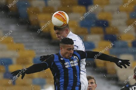 Brugge's Nabil Dirar, front, jumps for the ball with Dynamo Kyiv's Denys Popov during the Europa League round of 32 first leg soccer match between Dynamo Kyiv and Brugge at the Olimpiyskiy Stadium in Kyiv, Ukraine