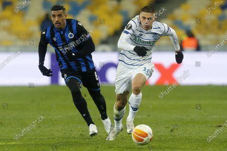 Dynamo Kyiv's Vitaliy Mykolenko, right, controls the ball by Brugge's Nabil Dirar during the Europa League round of 32 first leg soccer match between Dynamo Kyiv and Brugge at the Olimpiyskiy Stadium in Kyiv, Ukraine