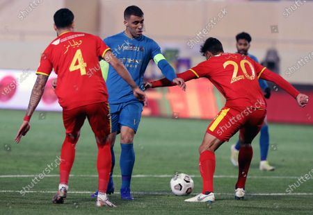 Al-Qadisiyah's players Rhys Williams (L) and Uros Vitas (R) in action against Al-Nassr's Abderazak Hamdallah (C) during the Saudi Professional League soccer match between Al-Qadisiyah and Al-Nassr at Prince Saud Bin Jalawy Stadium, in Al-Khobar, Saudi Arabia, 18 February 2021.
