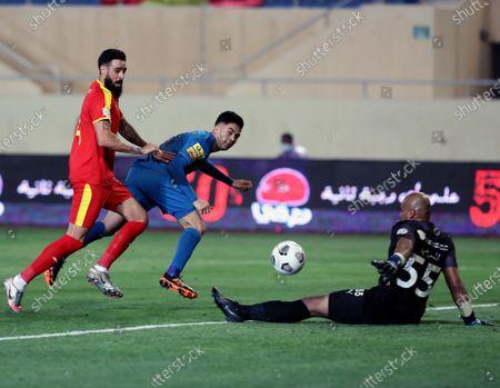 Al-Qadisiyah's player Rhys Williams (L) and goalkeeper Faisal Al-Masrahi (R) in action against Al-Nassr's Gonzalo Martinez (C) during the Saudi Professional League soccer match between Al-Qadisiyah and Al-Nassr at Prince Saud Bin Jalawy Stadium, in Al-Khobar, Saudi Arabia, 18 February 2021.