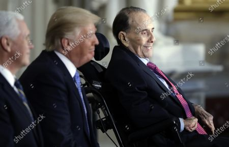 President Donald Trump, center and Vice President Mike Pence watch during a Congressional Gold Medal ceremony honoring former Senator Bob Dole on Capitol Hill in Washington. Political icon and 1996 Republican presidential nominee Bob Dole says he has been diagnosed with stage 4 lung cancer. The 97-year-old former U.S. Senate majority leader said Thursday in a short statement that he would begin treatment for the disease Monday